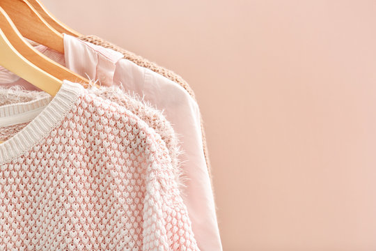 Apricot clothes on hangers against trendy color background