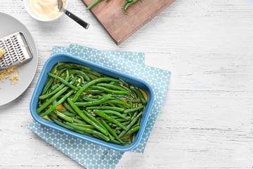 Baking dish with yummy green bean casserole on kitchen table