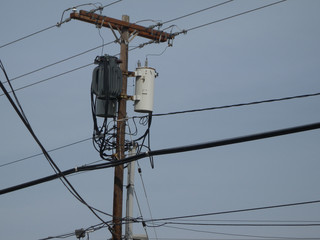 electricity pole with tangled wires and distribution transformer