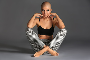 Beautiful bald woman sitting against grey background