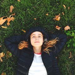 ragazza sdraiata sull'erba guarda il cielo