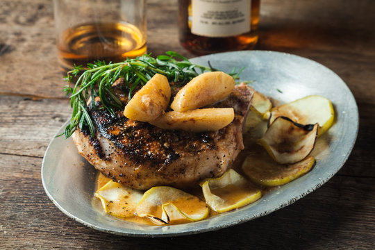 Grilled pork chop with bourbon spiced maple apples served with roasted potatoes