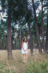 Little girl in a white dress standing in the woods