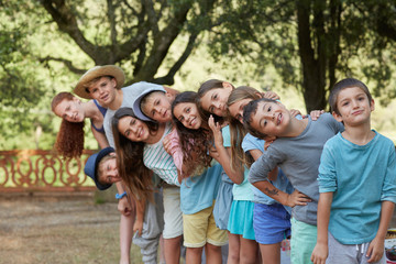 Group portrait of ten children at an outdoors party in a fun mood