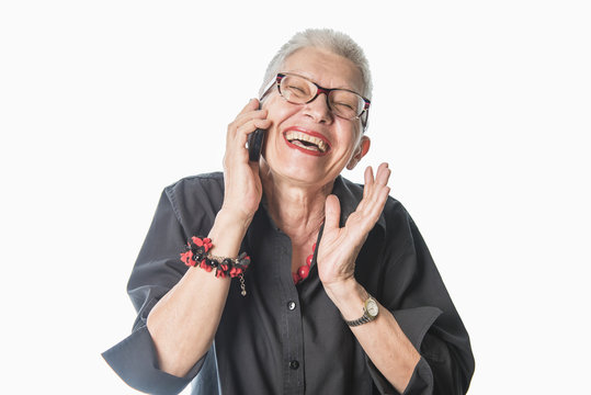 Senior elderly lady laughing to a wonderful conversation she's having on her cell phone, white background