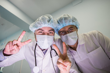 Two cheerful doctors above the camera show hand sign peace