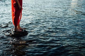 Woman in red dress standing on rock in sea Fototapete