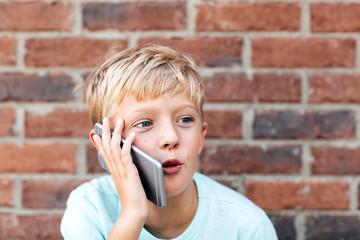 expressive boy talking on a phone