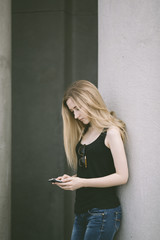 blond woman holding a cell phone outdoors