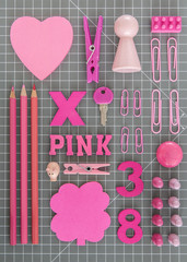 Pink toys and office tools on grey background