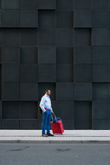 Businessman with the suitcase standing at the city street