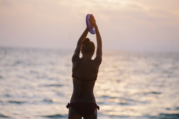 Woman on the beach playing frisbee