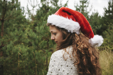 Young woman with christmas hat shot from behind, outdoors