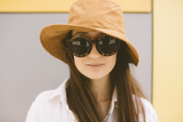 funny summer portrait of young woman with hat and round sunglasses
