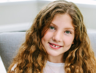 Girl with long curly hair, smiling.