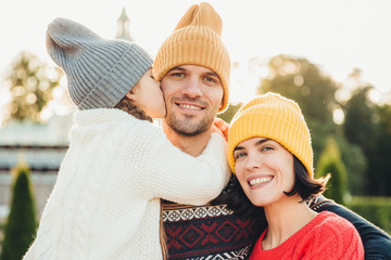 Sincere emotions. Little cute girl in knitted hat and white warm sweater kisses her father with love. Friendly affectionate couple pose together outdoors, smile happily, have wonderful relationships