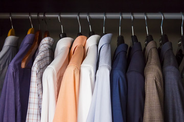 Row of colorful clean, pressed shirts in a closet
