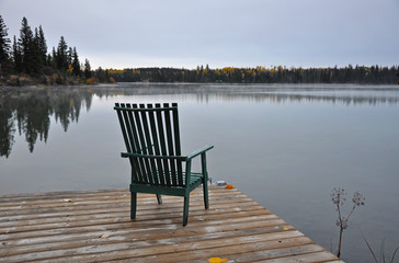 Empty chair on autumn morning by scenic lake