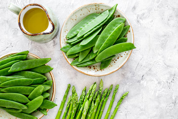 Healthy vegetarian food. Asparagus and pea near a jug of oil on grey stone background top view copyspace