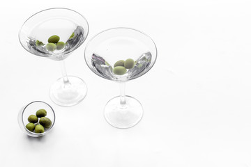 Martini cocktail in glass with olives at the bottom on white background top view copyspace