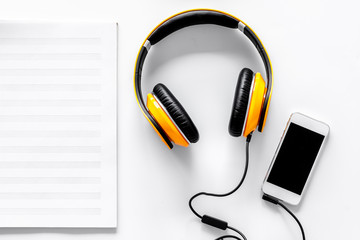 Worktable of composer today. Headphones, phone, music notes on white background top view