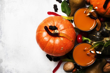 Halloween background with pumpkin juice, disgusting worms and black sweets, top view
