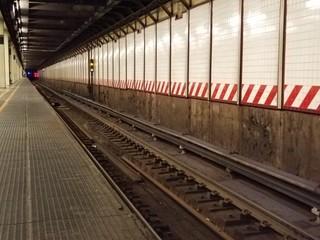 Underground subway platform with train tracks in a tunnel