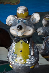 A vintage bear that is part of a merry-go-round children's ride. The bear has a bow tie, bowler hat and buck teeth.