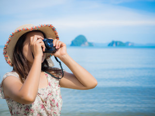 Close up beautiful woman with retro hipster camera having fun at the beach. Summer and travel concept.