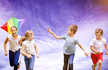 Composite image of full length of boy holding kite running with