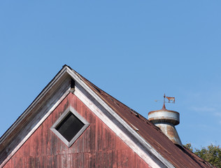 Close up of a weathered, rusty vintage weather vane that shows an arrow and a cow. It is atop an old red barn and against blue sky.