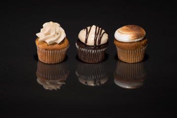 Three cupcakes on a dark reflective surface