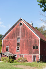 Old Red Barn in disrepair with a cow weather vane on its roof. Blue sky above barn provides copy space.