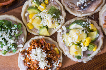 Mexican sopes with cotija cheese and salsa on wooden surface