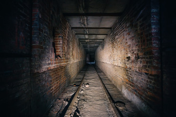 Dark scary corridor in abandoned industrial ruined brick factory, creepy interior