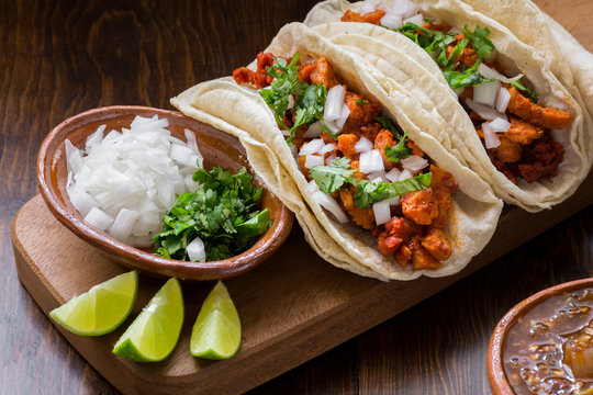 Authentic Mexican tacos with onions, cilantro and lime on wooden surface