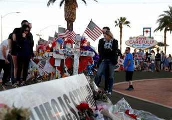 """People look over 58 wood crosses, with the names and photos of the October 1 mass shooting victims, in the median of Las Vegas Boulevard South near the """"Welcome to Las Vegas"""" sign in Las Vegas"""