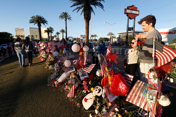 """Taylor Perkins, (R) a friend of shooting victim Cameron Robinson, stands by 58 wood crosses, with the names and photos of the October 1 mass shooting victims, in the median of Las Vegas Boulevard South near the """"Welcome to Las Vegas"""" sign in Las Vegas"""
