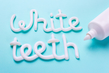 Words white teeth from toothpaste. Tube and toothbrush for cleaning teeth and whitening