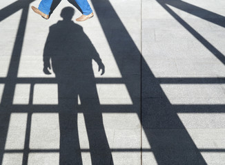 shadow of a man on the sidewalk among the beams, visible someone's feet
