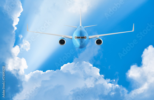 Canvas Prints Airplane flying in the blue sky among clouds and sunlight