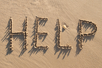 Help word drawn on wet sand by the waves on the shore. Background.