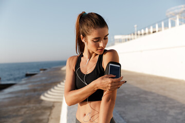 Smiling young sports woman listening music using mobile phone.
