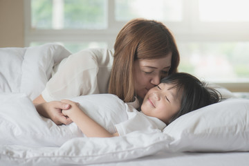 mother  kissing her son on white bed