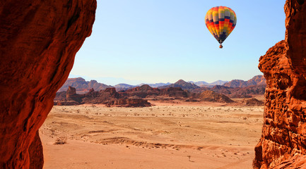 Colorful hot air balloon flight in the blue sky in beautiful landscape of multicolored stony desert with rocks. Timna geological park. Israel