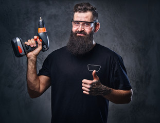 A man holds a drill over grey background.