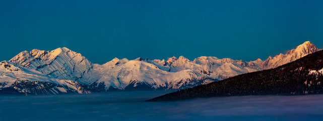 Scenic panorama sunset landscape of Crans-Montana range in Swiss Alps mountains with peak in background, Crans Montana, Switzerland.