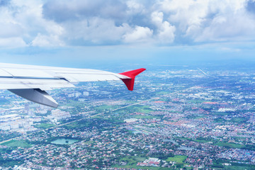 Scenery from airplane 's window seeing wing of airplane white clouds , blue sky and landscape of Bangkok , Thailand