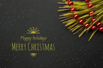 Unique Christmas or New Year card. Black paper board closeup with pine brunch and red garland and text merry christmas in White color.  Frame image for seasonal greeting card.