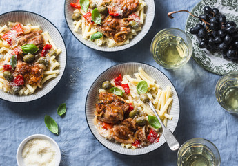 Italian food table. Pasta with slow cooker chicken with olives and sweet peppers, white wine. On a blue background, top view